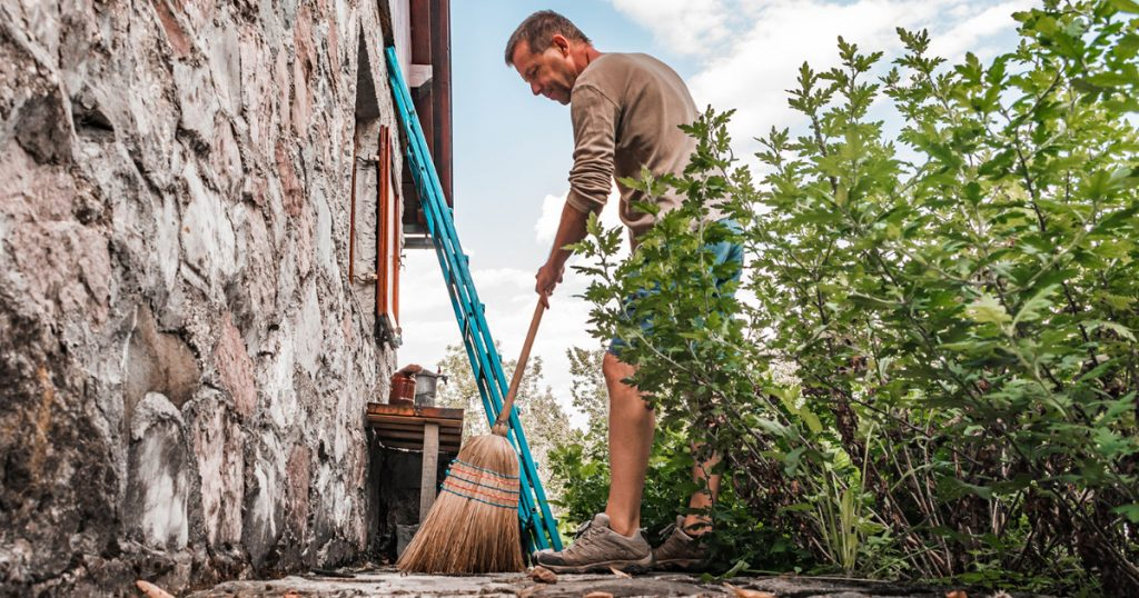 businessman sweeping the outside of his house