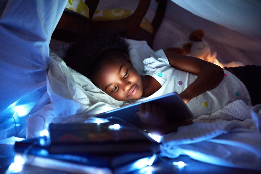 young girl looking at tablet under a pillow fort with string lights