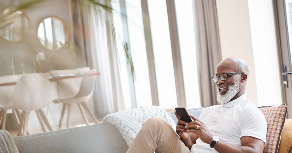 African American man sitting on couch scrolling through phone
