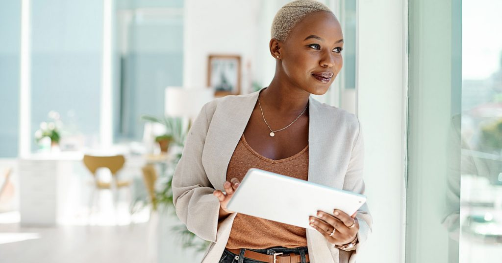 young black young businesswoman using a digital tablet while looking out the window in an office