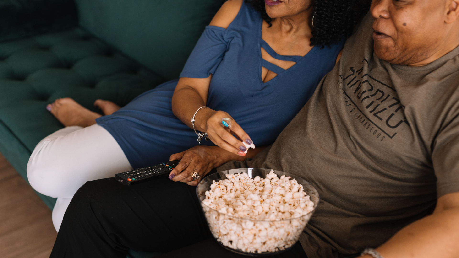 Man and woman watching Netflix on cough while eating popcorn