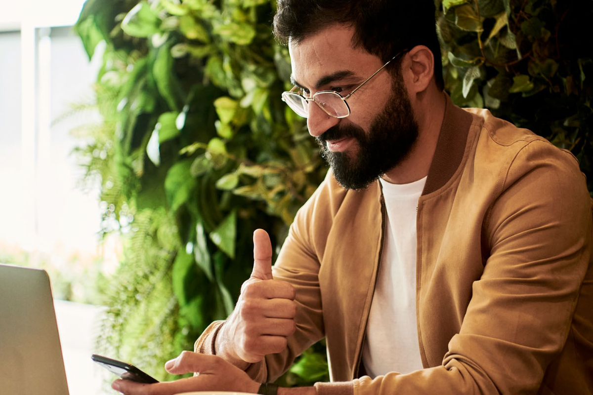 young business man in yellow jacket giving thumbs up to computer screen
