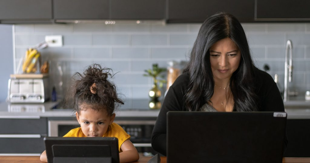 Woman remote worker on laptop while daughter is sitting next to her