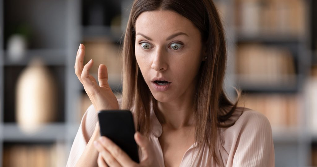 Woman with a shocked look looking at her phone