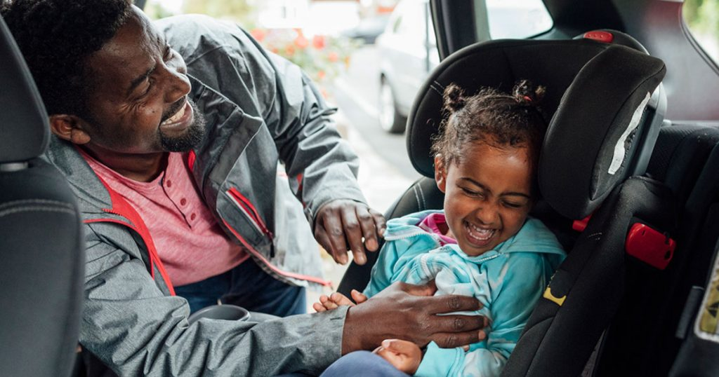 Dad tickling daughter in car seat. both laughing and having fun before the head out on a road trip that the dad planned after researching on his computer