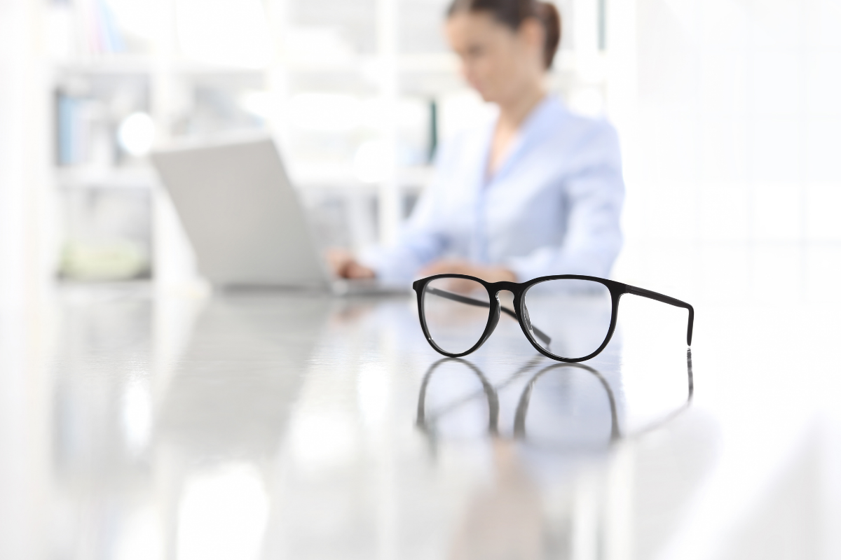 Woman on computer with glasses in foreground